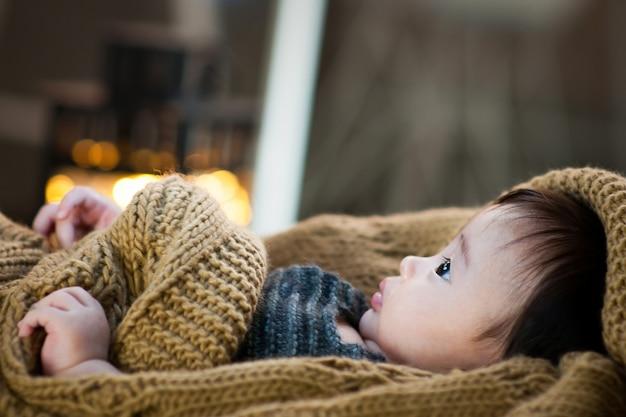 Het is de zijkant van een baby die een bruine deken draagt.