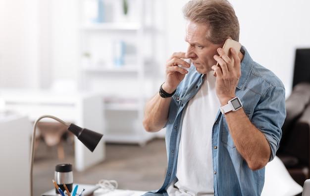 Het is een belangrijke oproep. ernstige man zit in halve positie op zijn tafel, naar beneden kijkend terwijl hij zijn neus afveegt