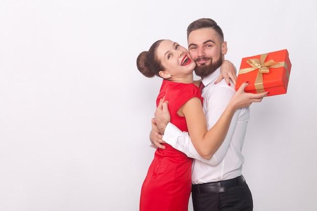 Het is een cadeau voor jou, een knuffelende vrouw met een geschenkdoos