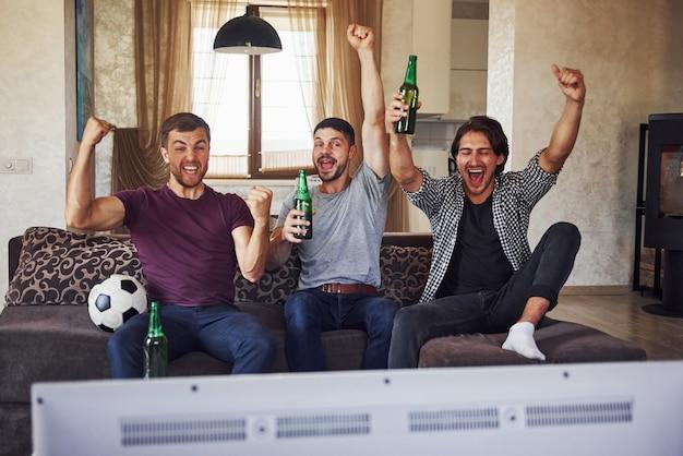 Het is een doel. opgewonden drie vrienden die samen thuis voetbal kijken op tv.