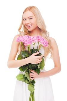 Het is een grote dag voor mij! mooie jonge blonde haarvrouw die een boeket met roze rozen vasthoudt en glimlacht terwijl ze op wit wordt geïsoleerd