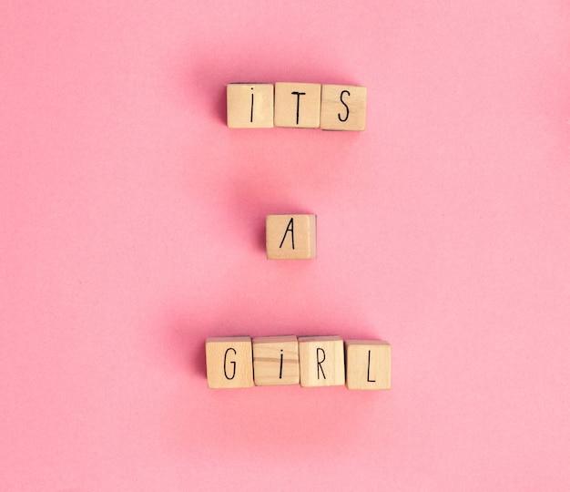 Het is een meisjestekst geschreven met houten blokjes op een pastel witte achtergrond bovenaanzicht, babyaankondiging. plat leggen, tekstruimte. wenskaart, douche, baby concept helder kleurrijk ontwerp schattig