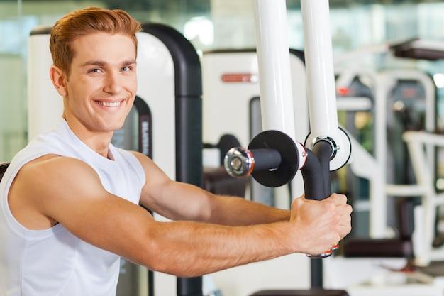 Het is erg belangrijk om fit te blijven. knappe jonge man aan het trainen in de sportschool en glimlachen