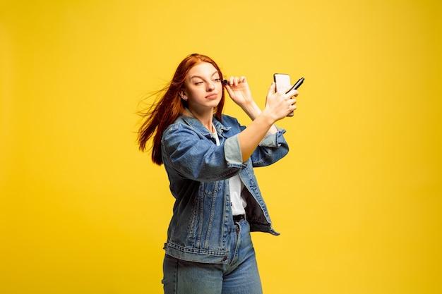 Het is gemakkelijker om een volgeling te zijn. geen selfie nodig voor make-up. kaukasische vrouw portret op gele achtergrond. mooi vrouwelijk rood haarmodel. concept van menselijke emoties, gezichtsuitdrukking, verkoop, advertentie.
