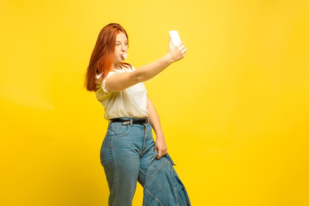 Het is gemakkelijker om een volgeling te zijn. minimale kleding nodig voor selfie. kaukasische vrouw portret op gele achtergrond. mooi vrouwelijk rood haarmodel. concept van menselijke emoties, gezichtsuitdrukking, verkoop, advertentie.