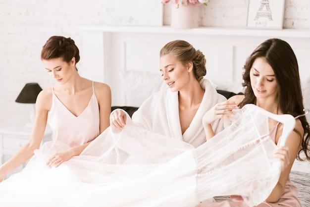 Het is geweldig. doordachte vrolijke jonge bruid zittend op het witte bed thuis met de bruidsmeisjes en tederheid uiten terwijl je je klaarmaakt en de trouwjurk vasthoudt