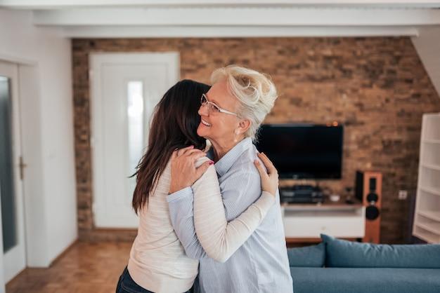 Het is heerlijk om je te zien. volwassen moeder en dochter die thuis koesteren.