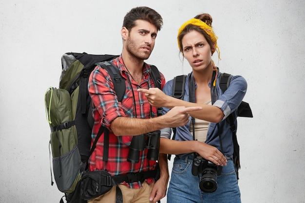 Het is helemaal jouw schuld. foto van boze mannelijke en vrouwelijke wandelaars of toeristen die zijn uitgerust met reizende spullen die met de vingers naar elkaar wijzen, elkaar de schuld geven voor het verdwalen tijdens een wandeltocht