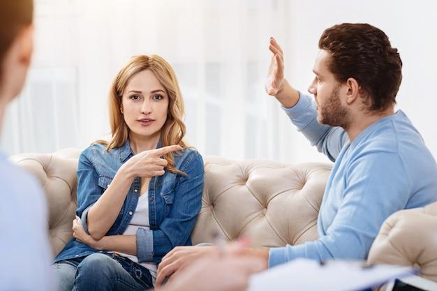 Het is hem. leuke positieve prettige vrouw zittend op de bank en wijzend naar haar man tijdens een bezoek aan een psycholoog met hem
