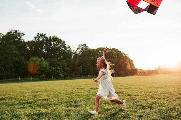 Het is hier warm, maar de wind helpt om te verfrissen. gelukkig meisje in witte kleren veel plezier met vlieger in het veld. prachtige natuur.