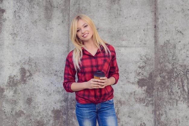 Het is koffietijd! koffie tijd concept. vrouw met stralende glimlach koffie drinken. close-up portret, grijze muur