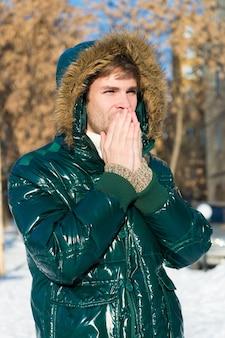 Het is koud buiten. bos in sneeuw. verse lucht. sneeuwachtig weer. trendy winterjas. man op wintervakantie. vakantie en reizen in de winter. wintermode. warme kleding. man. warm krijgen.