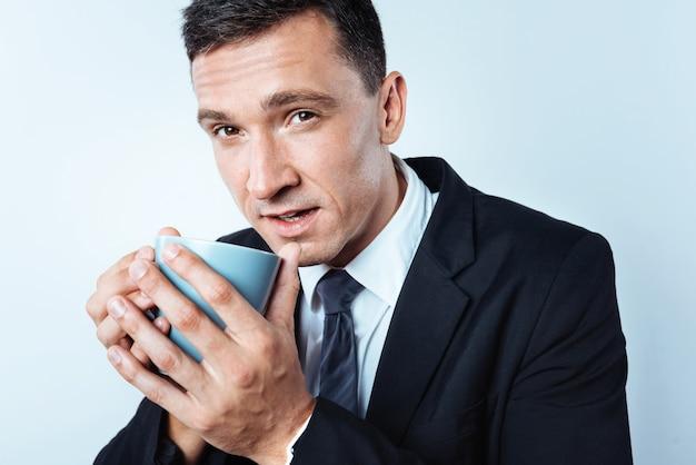 Het is koud buiten. opgeschaald van een opname van een volwassen man die in de camera kijkt terwijl hij een kopje vasthoudt en probeert op te warmen met een slokje van een aromatische koffie.