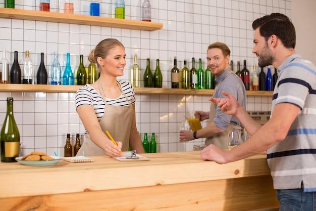 Het is lunchtijd. vrolijke aardige positieve man die naar de serveerster kijkt en een bestelling plaatst tijdens de lunch in het café