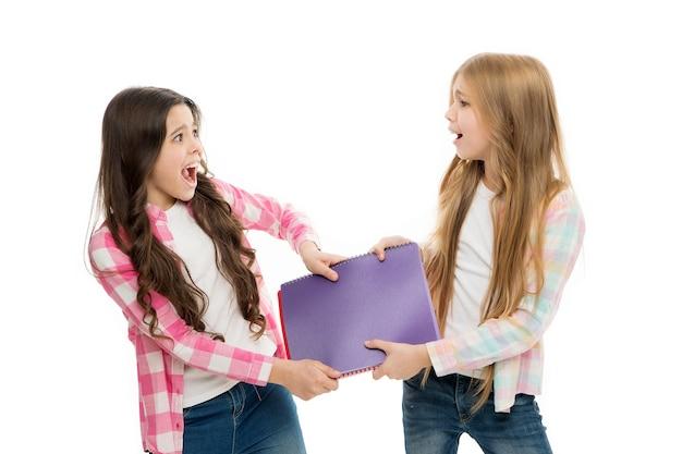 Het is mijn huiswerk. kleine leerlingen kunnen hun huiswerkagenda en notitieboek niet met hen delen. stoute schoolmeisjes in de huiswerkclub op school. kleine schoolkinderen vechten om huiswerkopdracht.