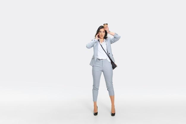 Het is nu jouw hoofdpijn. jonge vrouw in grijs pak krijgt schokkend nieuws van baas of collega's. verdoofd kijken terwijl je koffie laat vallen. concept van de problemen van de kantoormedewerker, zaken, stress.