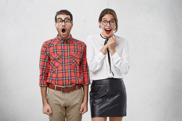 Het is ongelooflijk! geschokte man kijkt verbaasd door een bril, houdt zijn mond open, hoort onverwacht nieuws en is blij
