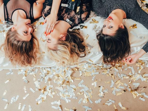 Het is ons geheim. feestvrouwen kletsen. hangout-vrouwtjes die ondersteboven liggen en roddels uitwisselen. verspreide confetti rond.