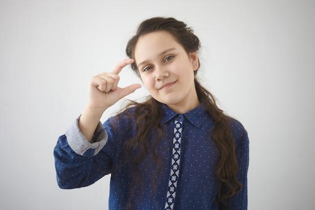 Het is te klein. portret van kaukasisch mooi meisje in stijlvol overhemd gebaren alsof je iets kleins tussen wijsvinger en duim vasthoudt