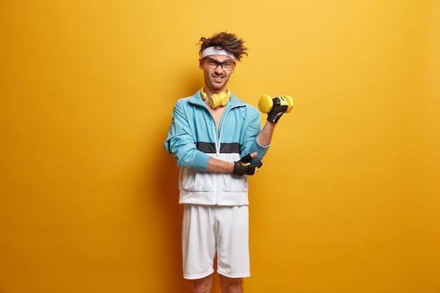 Het is te moeilijk voor mij. vastberaden man tilt dumbbells op met intense expressie, gaat thuis sporten, blijft fit met een goed lichaam en sport, is gezond, draagt actieve kleding, geïsoleerd op een gele muur