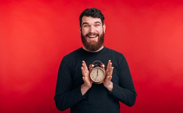 Het is tijd happy bebaarde man houdt een wekker op de rode muur.