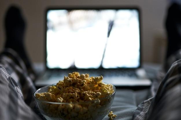 Het is tijd om te chillen close-up shot van popcorn in een kom man in pyjama kijken naar online film met behulp van