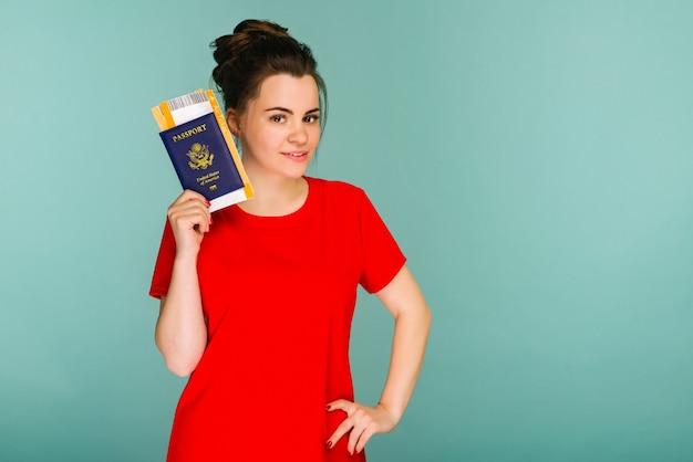 Het is tijd om te reizen. een moderne trendy lachende vrouw in een rode jurk met vliegtickets en een paspoort in haar hand.