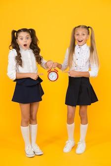 Het is tijd. schoolrooster. schoolmeisjes en wekker. kinderen scholieren. kennis dag. schooltijd. verrast geschokte kinderen houden de wekkertijd af. laatkomer wordt gestraft.