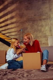 Het is van mij. gelukkige jonge blonde vrouw zittend op de vloer tijdens het uitpakken van de doos