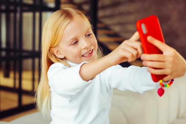 Het is van mij. schattig kind dat de telefoon in beide handen houdt terwijl het met plezier vrije tijd doorbrengt