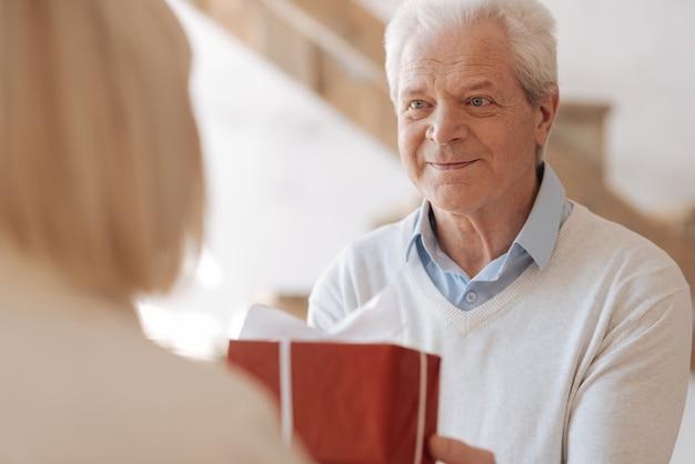 Het is voor jou. opgetogen positieve oudere man die een cadeau vasthoudt en het aan de zijne geeft terwijl hij naar haar kijkt