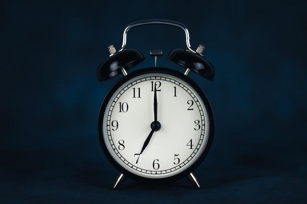 Het is zeven uur 's ochtends. tijd - 07-00. retro klok. donkere achtergrond. hijsconcept voor werk. kopieer de ruimte en knip uit.