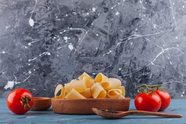 Het italiaanse nest van deegwarenfettuccine met verse rode tomaten en kruiden.
