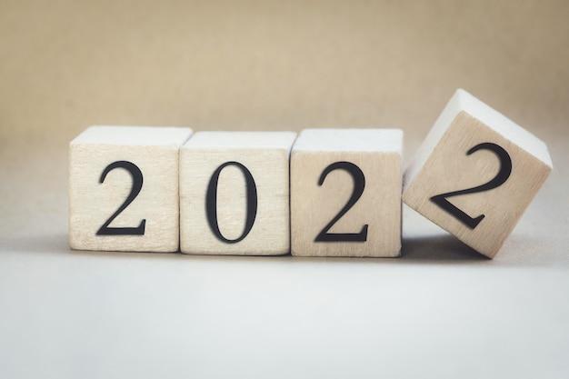 Het jaar geschreven op houten kubussen vinger flipping jaar tot jaar nieuwjaar concept achtergrond beginnen ...
