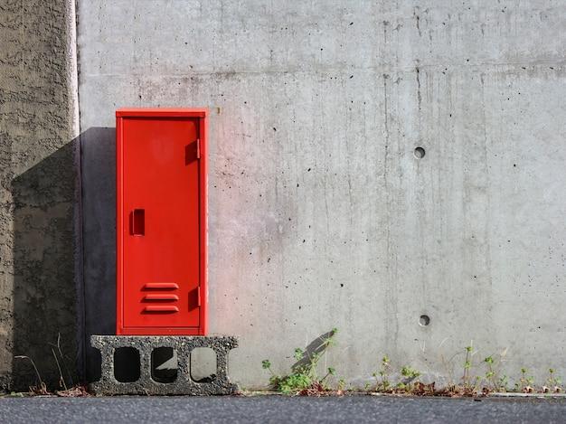 Het japanse rode brandblusapparaat houdt doos met cementmuur als achtergrond.