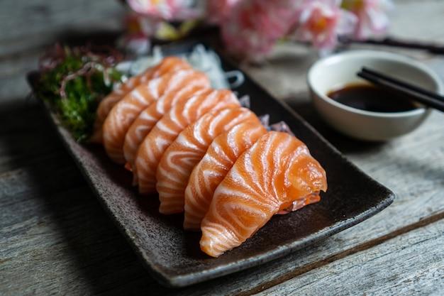 Het japanse voedsel van de zalmsashimi met sojasaus op houten lijst