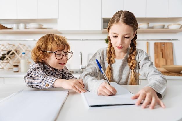 Het joch helpen. vriendelijke, slimme, liefdevolle zus die iets opschrijft om haar broertje te helpen met zijn thuistoewijzing terwijl ze allebei thuis zijn