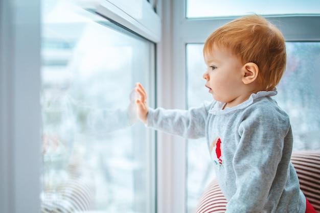 Het joch kijkt voorzichtig uit het raam naar de sneeuw