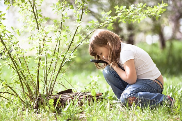 Het jong geitjemeisje met vergrootglas onderzoekt gras
