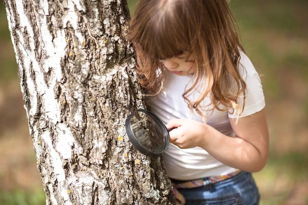 Het jong geitjemeisje onderzoekt schors van boomvergrootglas