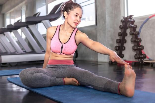 Het jonge aantrekkelijke de vrouw van azië uitrekken zich bij geschiktheidsgymnastiek.