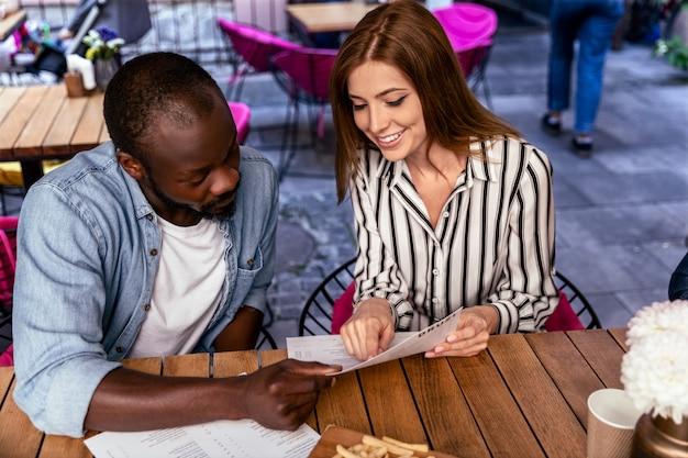 Het jonge aantrekkelijke kaukasische meisje en de afrikaanse jongen leren menu alvorens tot voedsel opdracht te geven