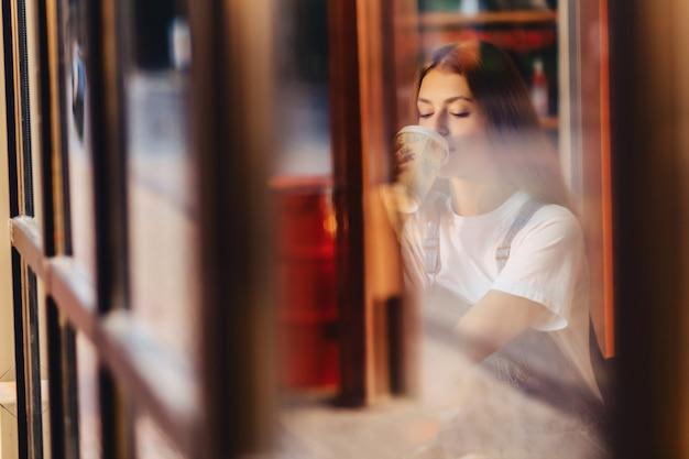 Het jonge aantrekkelijke mooie meisje bij koffie met koffie ontspant bij ochtend throuth glas