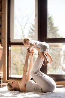 Het jonge aantrekkelijke sportieve moeder en babydochter uitoefenen