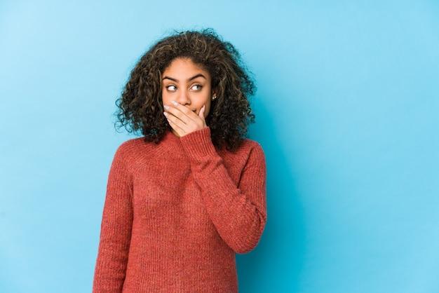 Het jonge afrikaanse amerikaanse krullende haarvrouw nadenkende kijken aan een exemplaarruimte die mond behandelen met hand.