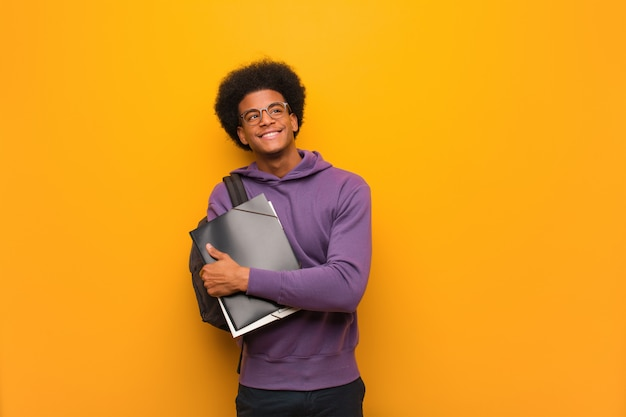 Het jonge afrikaanse amerikaanse studentenmens zeker glimlachen en kruisend wapens, omhoog kijkend
