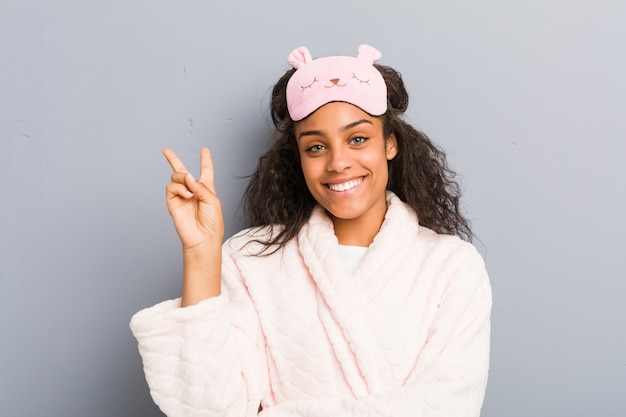 Het jonge afrikaanse amerikaanse vrouw dragen pyjama's en een slaapmasker die nummer twee met vingers tonen.