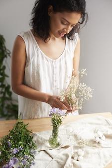 Het jonge afrikaanse vrouwelijke bloemist glimlachen die met bos van bloemen op het werk over witte muur werkt.
