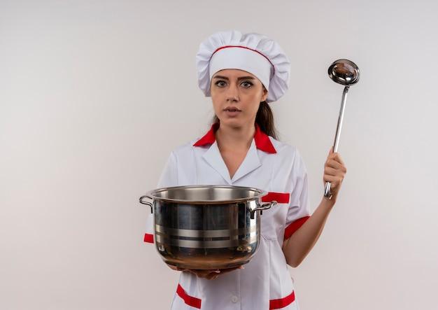 Het jonge angstige kaukasische kokmeisje in eenvormige chef-kok houdt pot en pollepel die op witte achtergrond met exemplaarruimte wordt geïsoleerd