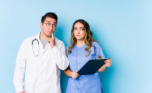 Het jonge artsenpaar stellen in een blauwe geïsoleerde muur zijdelings het kijken met twijfelachtige en sceptische uitdrukking.